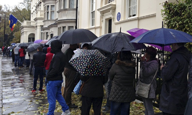 Romanians wait in line to enter a polling station at the Romanian embassy in London